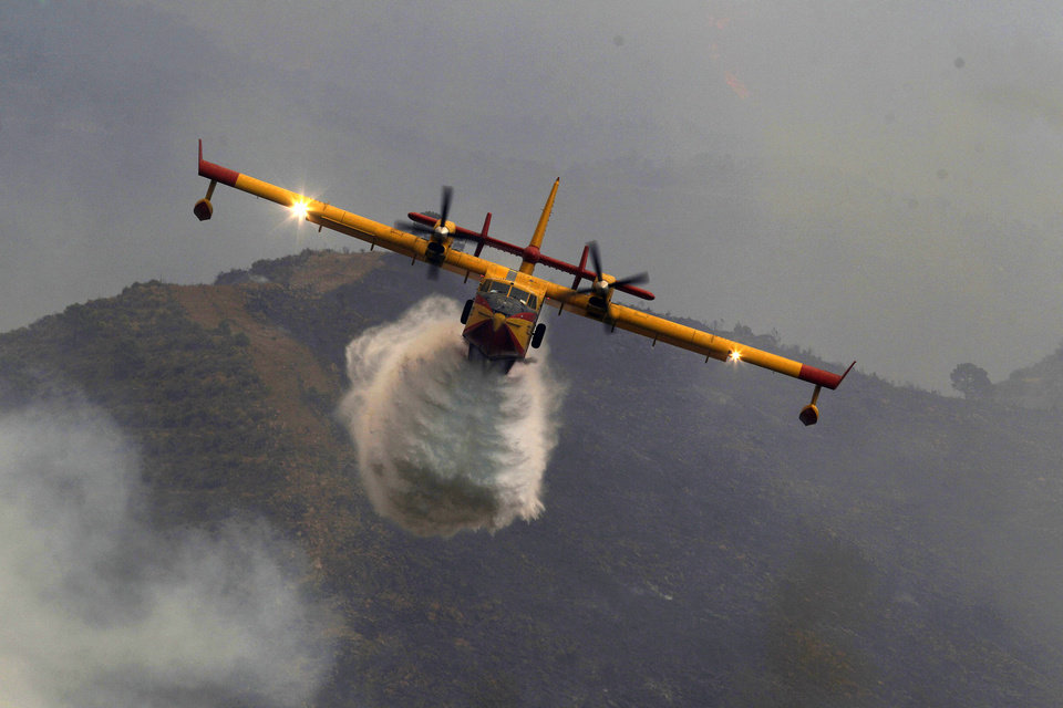 Photo -   A firefighting plane dumps water on a raging forest fire in Ojen, southern Spain, Friday, Aug. 31, 2012. Spanish officials say some 4,000 people have been evacuated from their houses as a wildfire abetted by strong winds spread rapidly through hills around the popular southern tourist city of Marbella. (AP Photo/Sergio Torres)