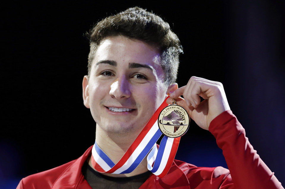 Photo - Max Aaron holds the gold medal after winning the senior men's championship at the U.S. figure skating championships, Sunday, Jan. 27, 2013, in Omaha, Neb. (AP Photo/Charlie Neibergall)