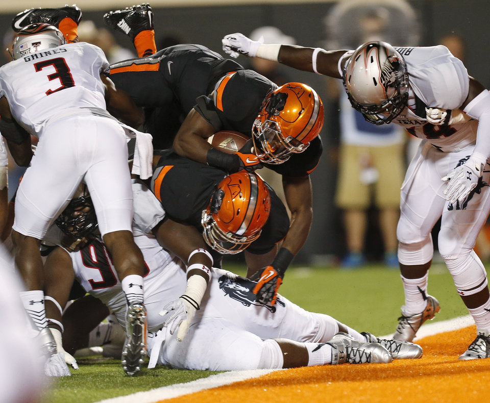 Photo - Oklahoma State's Desmond Roland (26) leaps over the pile and into the end zone for a second-quarter touchdown during a college football game between the Oklahoma State Cowboys (OSU) and the Texas Tech Red Raiders at Boone Pickens Stadium in Stillwater, Okla., Thursday, Sept. 25, 2014. Photo by Nate Billings, The Oklahoman