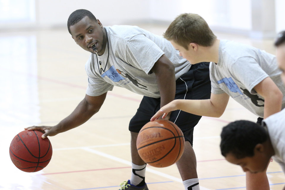 Photo - Coach Jerrame Dockery works with kids participating in a Down Syndrome Association of Central Oklahoma basketball camp at Chesapeake Energy's fitness center in Oklahoma City, Friday July  25 , 2014. Photo By Steve Gooch, The Oklahoman