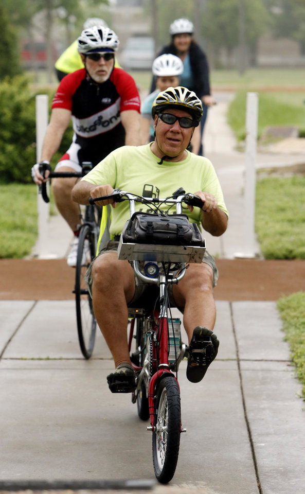 Photo - Frank Lotito, of Noble, rides his electric and pedal power bicycle to the Bike to Work rally Friday at Andrews Park in Norman. PHOTO BY STEVE SISNEY, THE OKLAHOMAN  STEVE SISNEY