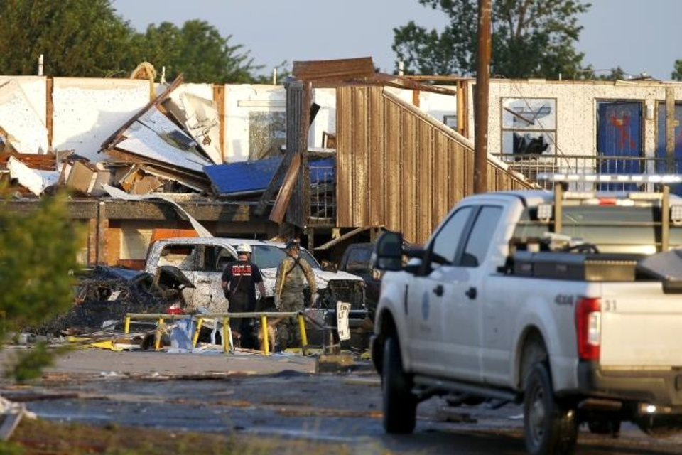 Photo -  Workers look through tornado damage at the American Budget Value Inn in El Reno, Okla., Sunday, May 26, 2019. The deadly tornado leveled a motel and tore through the mobile home park near Oklahoma City overnight. (Bryan Terry/The Oklahoman via AP)