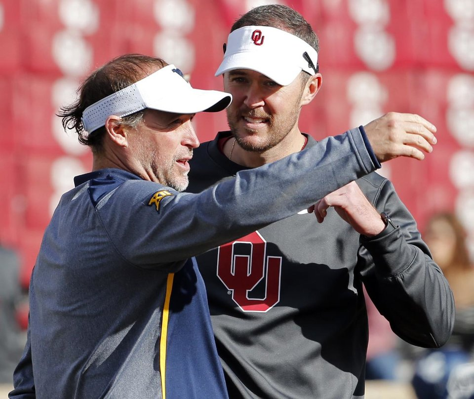 Photo -  West Virginia head coach Dana Holgorson and Sooner head coach Lincoln Riley talk before a college football game between the University of Oklahoma Sooners (OU) and the West Virginia Mountaineers at Gaylord Family-Oklahoma Memorial Stadium in Norman, Okla., on Saturday, Nov. 25, 2017. Photo by Steve Sisney, The Oklahoman