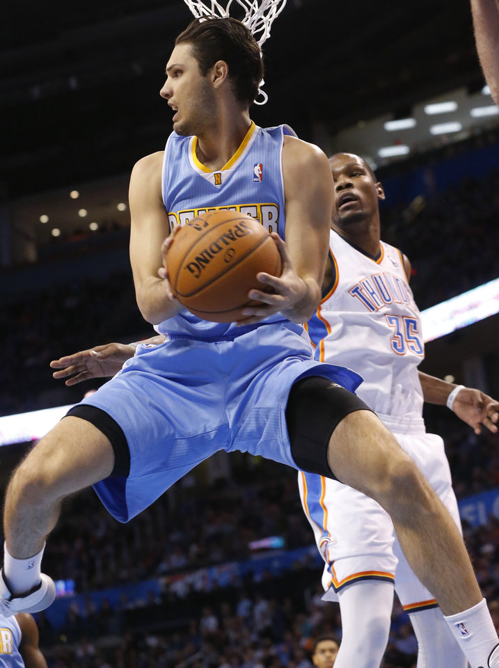 Photo - Denver Nuggets guard Evan Fournier drives under the basket past Oklahoma City Thunder forward Kevin Durant (35) in the first quarter of an NBA basketball game in Oklahoma City, Monday, March 24, 2014. (AP Photo/Sue Ogrocki)