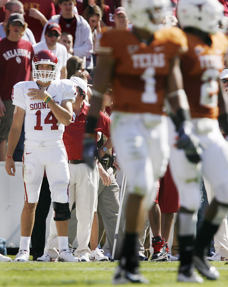 Photo - Oklahoma's Sam Bradford (14) holds his shoulder as he looks on from the sideline after being injured during the Red River Rivalry college football game between the University of Oklahoma Sooners (OU) and the University of Texas Longhorns (UT) at the Cotton Bowl in Dallas, Texas, Saturday, Oct. 17, 2009. Photo by Chris Landsberger, The Oklahoman
