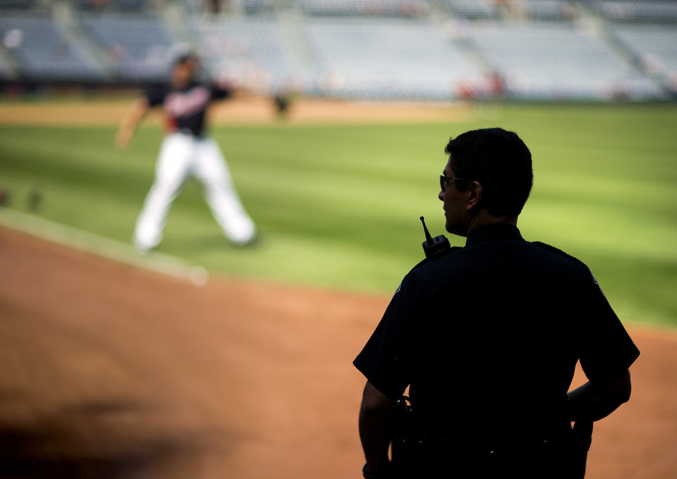 A police officer stands guard in the outfield as Atlanta Braves pitcher Jordan Walden warms up at left before the start of a baseball game between the Braves and the Kansas City Royals, Wednesday, April 17, 2013, in Atlanta. Signs of increased security were visible in the wake of the Boston Marathon explosions. (AP Photo/David Goldman)
