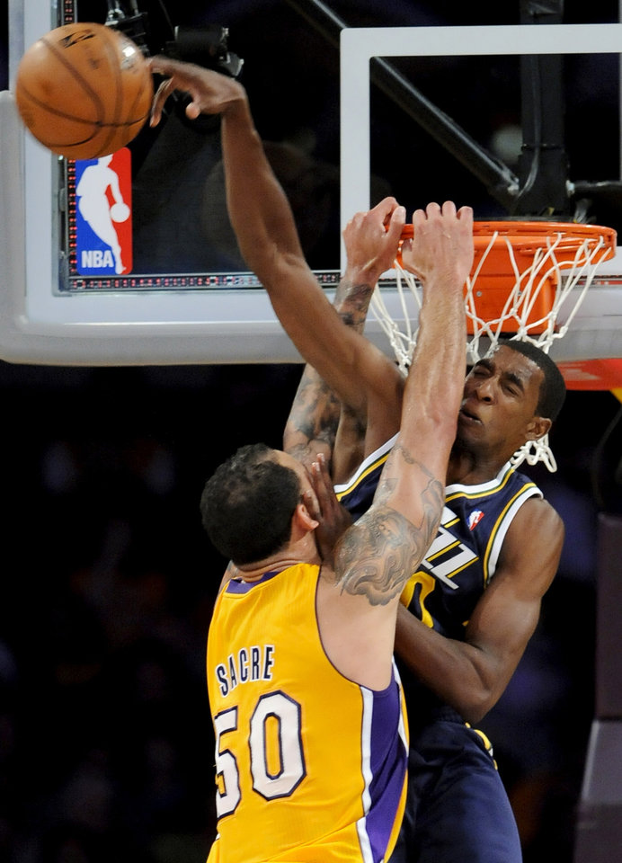 Photo -   Los Angeles Lakers center Robert Sacre (50) and Utah Jazz forward Jeremy Evans, right, collide at the basket during the first half of an NBA preseason basketball game, Saturday, Oct. 13, 2012, in Los Angeles. (AP Photo/Gus Ruelas)