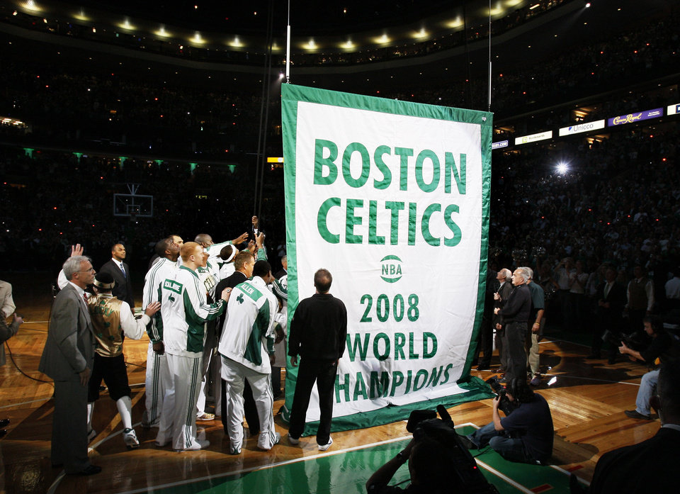 Photo - The Boston Celtics players and team personnel gather around to raise the Celtics' 17th NBA Championship banner during ceremonies prior to their opening night NBA basketball game against the Cleveland Cavaliers in Boston, Tuesday, Oct. 28, 2008. (AP Photo/Winslow Townson) ORG XMIT: MAEA101