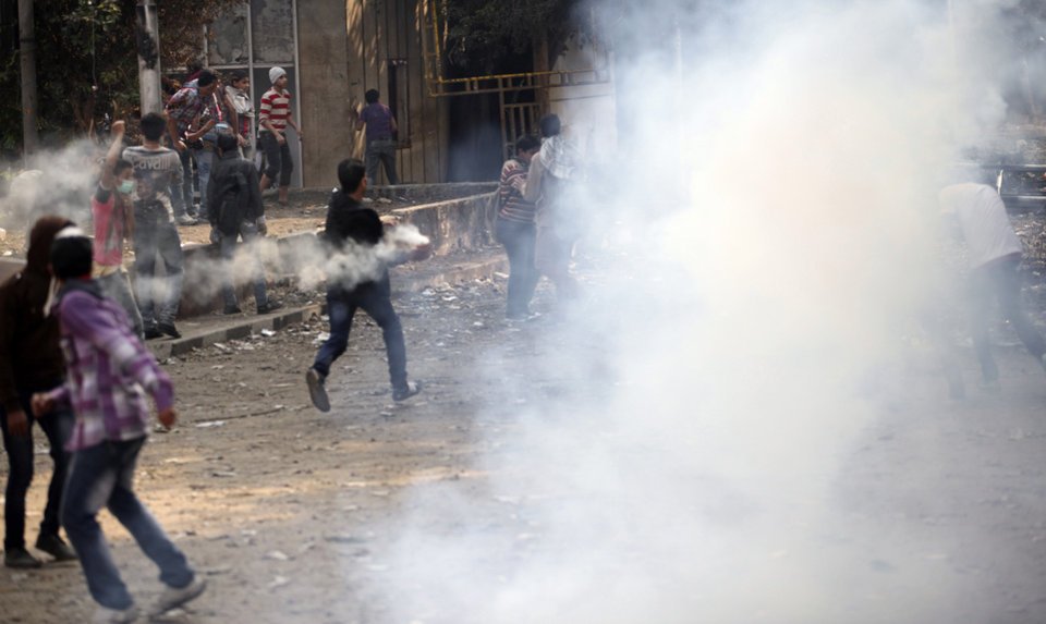 Photo -   Egyptians clash with security forces and attempt to throw back tear gas canisters fired at them near Tahrir square, where an opposition rally has been called for to voice rejection of President Morsi's seizure of near absolute powers, in Cairo, Egypt, Tuesday, Nov. 27, 2012. The Health Ministry said about 444 people have been wounded nationwide, including 49 who remain hospitalized, since the clashes erupted on Friday, according to a statement carried by the official news agency MENA. (AP Photo/Thomas Hartwell)