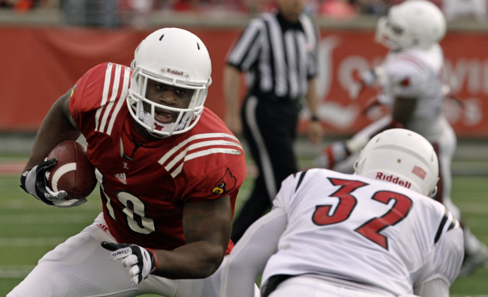 Photo - Louisville's Gerald Christian, left, works against defensive end Stacy Thomas (32) in a NCAA college spring football game in Louisville, Ky., Friday, April 11, 2014.  (AP Photo/Garry Jones)