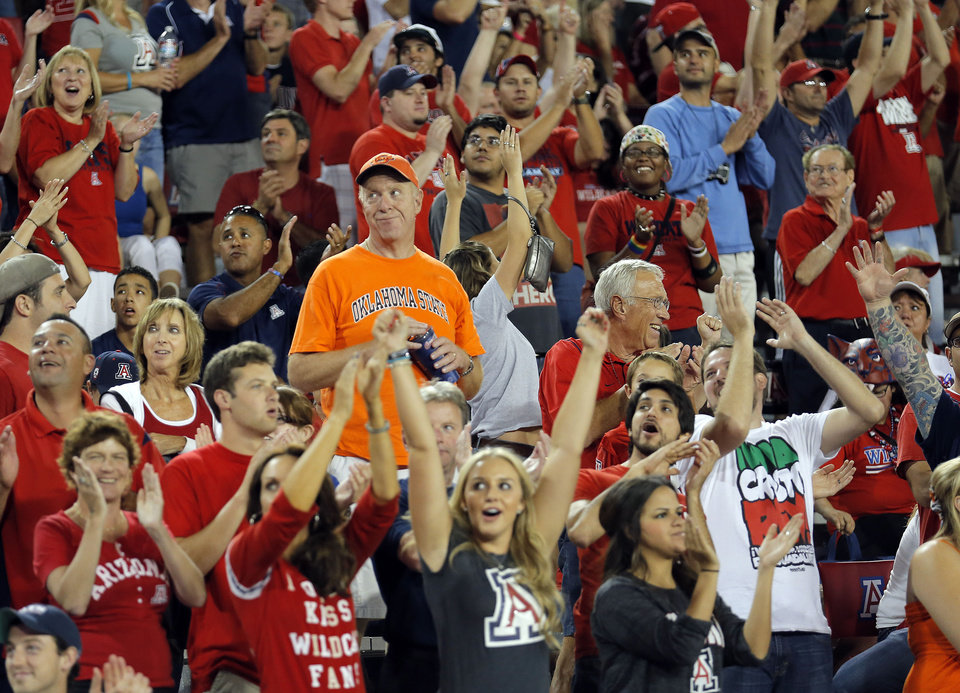 Photo - A OSU fans is surrounded by cheering Arizona fans during the college football game between the University  of Arizona and Oklahoma State University at Arizona Stadium in Tucson, Ariz.,  Sunday, Sept. 9, 2012. Photo by Sarah Phipps, The Oklahoman