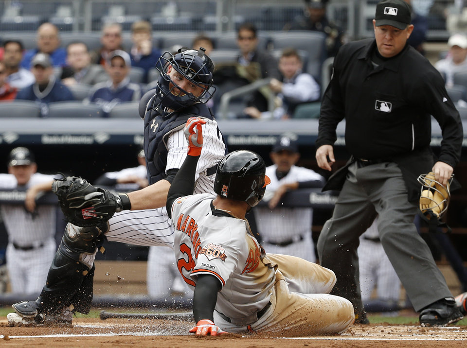 Photo - New York Yankees catcher Brian McCann, left, and home plate umpire Todd Tichenor watch as Baltimore Orioles Nick Markakis (21) scores on a sacrifice fly hit by Baltimore Orioles first baseman Chris Davis in the first inning of a baseball game at Yankee Stadium in New York, Tuesday, April 8, 2014.  (AP Photo/Kathy Willens)