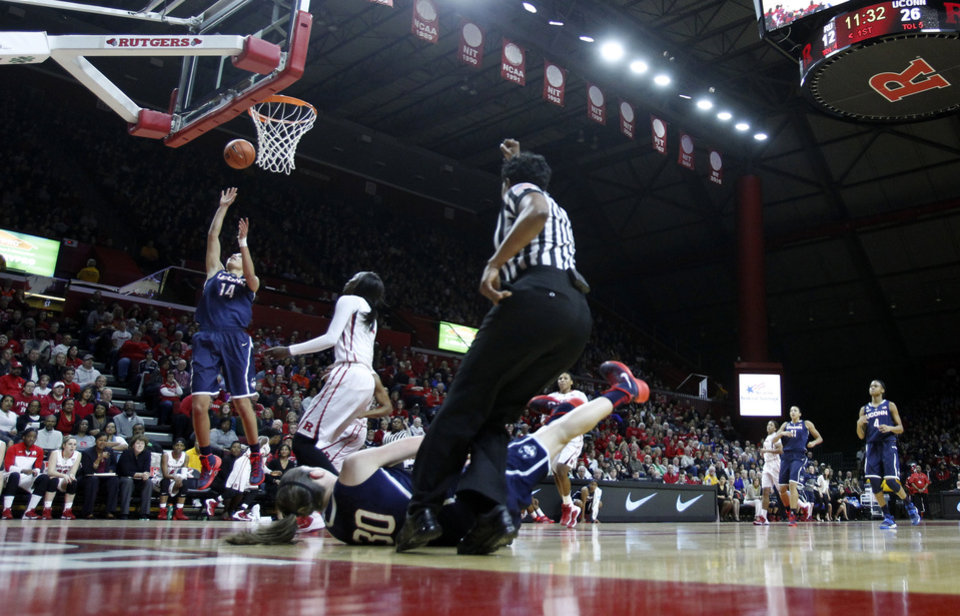 Photo - Connecticut guard Bria Hartley (14) takes a shot as teammate Breanna Stewart (30) falls during the first half of an NCAA women's college basketball game against Rutgers Sunday, Jan. 19, 2014, in Piscataway, N.J. Connecticut won 94-64. (AP Photo/Mel Evans)