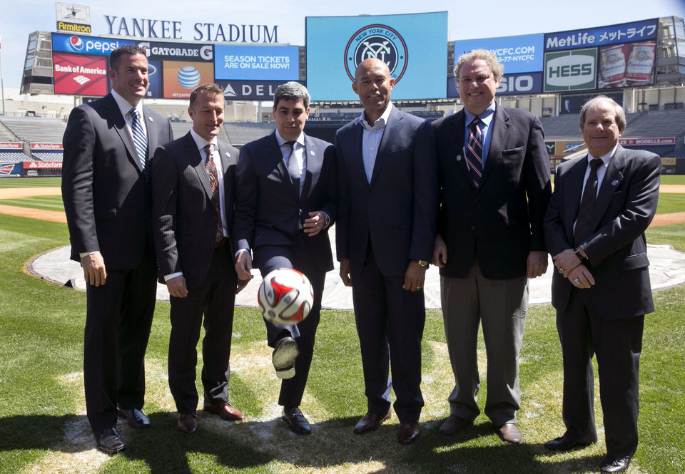 Photo - New York City Football Club soccer Chief Business Officer Tim Pernetti, head coach Jason Kreis, Director of Football Operations Claudio Reyna, retired New York Yankees pitcher Mariano Rivera, Yankees President Randy Levine, and Yankees COO Lonn Trost, left to right, pose for photos on the field at New York's Yankee Stadium, Monday, April 21, 2014. The Yankees announced that Yankee Stadium will serve as the Club's first home and begin play on March 2015. (AP Photo/Richard Drew)