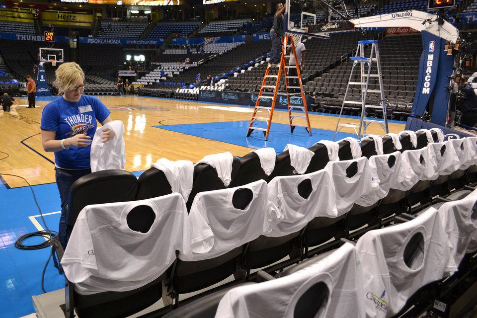 Photo - Nancy Cullen places tee shirts on chair backs at the Chesapeake Energy Arena for game two of the NBA Finals between the Oklahoma City Thunder and the Miami Heat Thursday June 14, 2012. Photo by Zeke Campfield, The Oklahoman