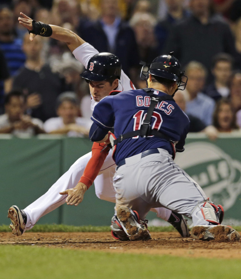 Photo - Boston Red Sox' Jacoby Ellsbury, left, reaches down towards home plate as he is tagged out by Cleveland Indians catcher Yan Gomes on a single by Dustin Pedroia during the third inning of a baseball game at Fenway Park in Boston, Thursday, May 23, 2013. (AP Photo/Charles Krupa)