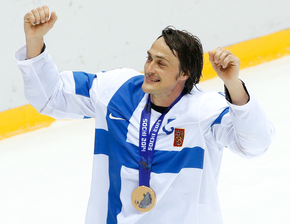 Photo - Teemu Selanne of Finland (8) takes a victory lap around the ice with his medal after he men's bronze medal ice hockey game at the 2014 Winter Olympics, Saturday, Feb. 22, 2014, in Sochi, Russia. Finland defeated the United States 5-0. (AP Photo/Matt Slocum)