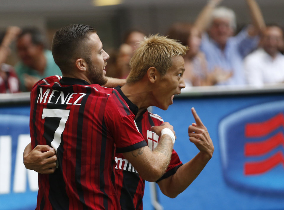 Photo - AC Milan forward Keisuke Honda, of Japan, right, celebrates with his teammate Jeremy Menez of France after scoring during a Serie A soccer match between AC Milan and Lazio, at the San Siro stadium in Milan, Italy, Sunday, Aug. 31, 2014. (AP Photo/Luca Bruno)