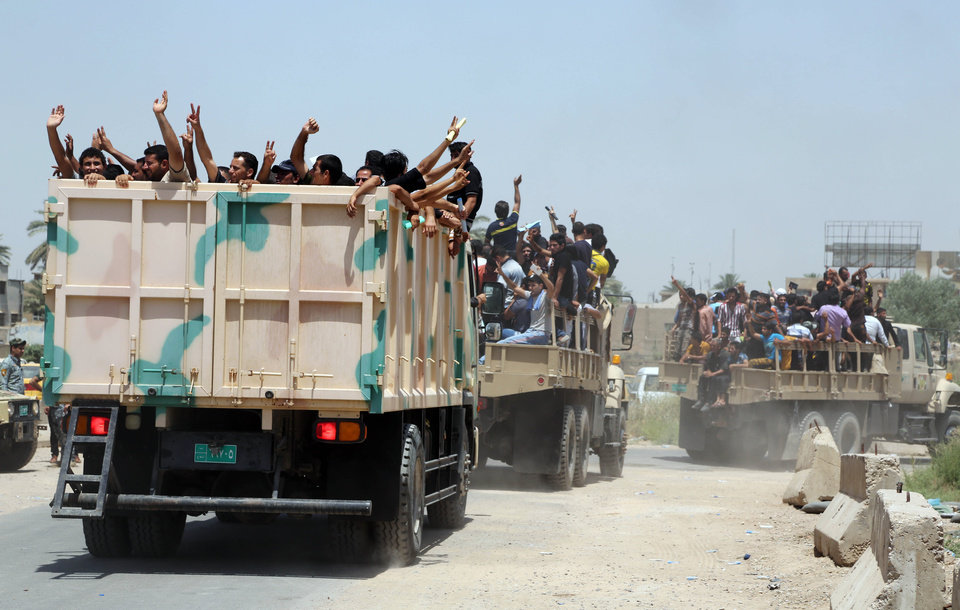 Photo - Iraqi men fill military trucks to join the Iraqi army at the main recruiting center in Baghdad, Iraq, Saturday, June. 14, 2014, after authorities urged Iraqis to help battle insurgents. Hundreds of young Iraqi men gripped by religious and nationalistic fervor streamed into volunteer centers across Baghdad Saturday, answering a call by the country's top Shiite cleric to join the fight against Sunni militants advancing in the north.(AP Photo/Karim Kadim)