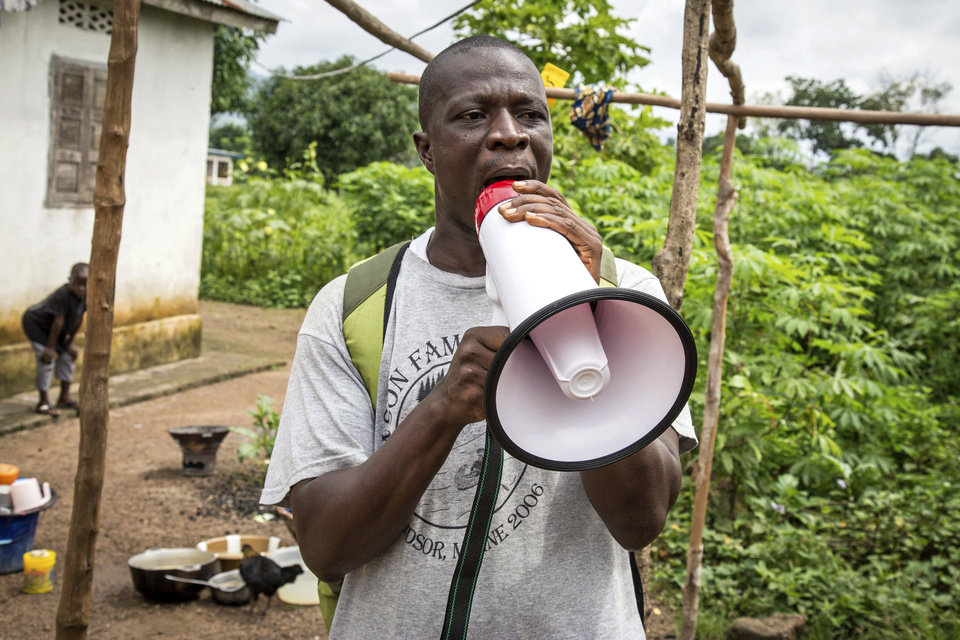 Photo - In this photo taken Monday, Aug. 11, 2014,  a community volunteer uses a megaphone to speak to villagers to raise Ebola awareness on the outskirts of Kenema, situated in the Eastern Province around 300 km, (186 miles),  from the capital city of Freetown in Kenema, Sierra Leone.  Over the decades, Ebola cases have been confirmed in 10 African countries, including Congo where the disease was first reported in 1976. But until this year, Ebola had never come to West Africa.  (AP Photo/ Michael Duff)