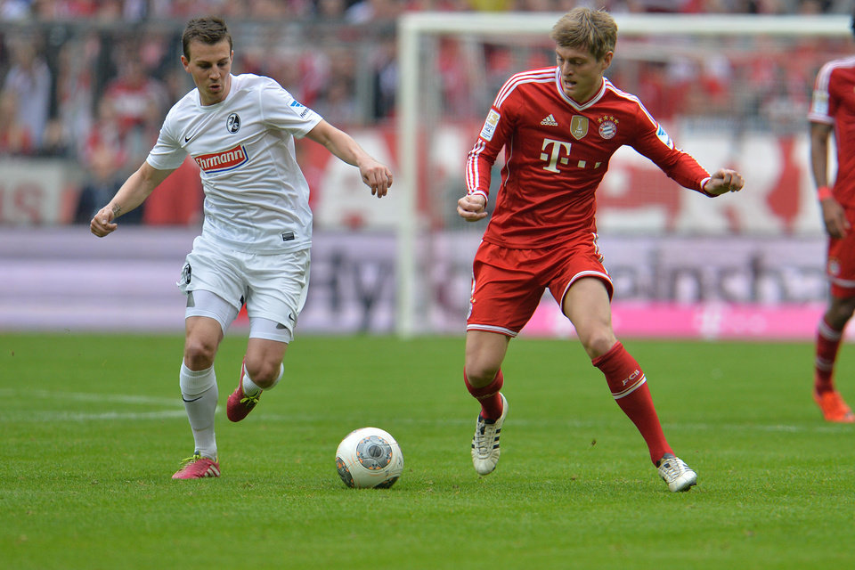 Photo - Bayern's Toni Kroos, right, and Freiburg's Vladimir Darida of Czech Republic challenge for the ball during the German first division Bundesliga soccer match between  FC Bayern Munich and SC Freiburg in Munich, Germany, on Saturday, Feb. 15, 2014. (AP Photo/Kerstin Joensson)