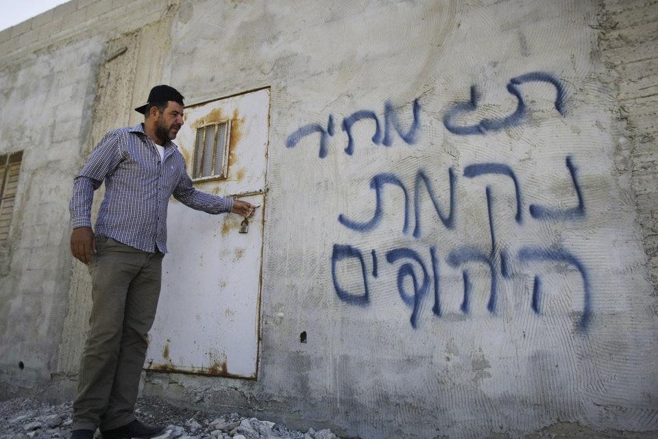 Photo - A Palestinian stands outside a house with Hebrew graffiti that reads,