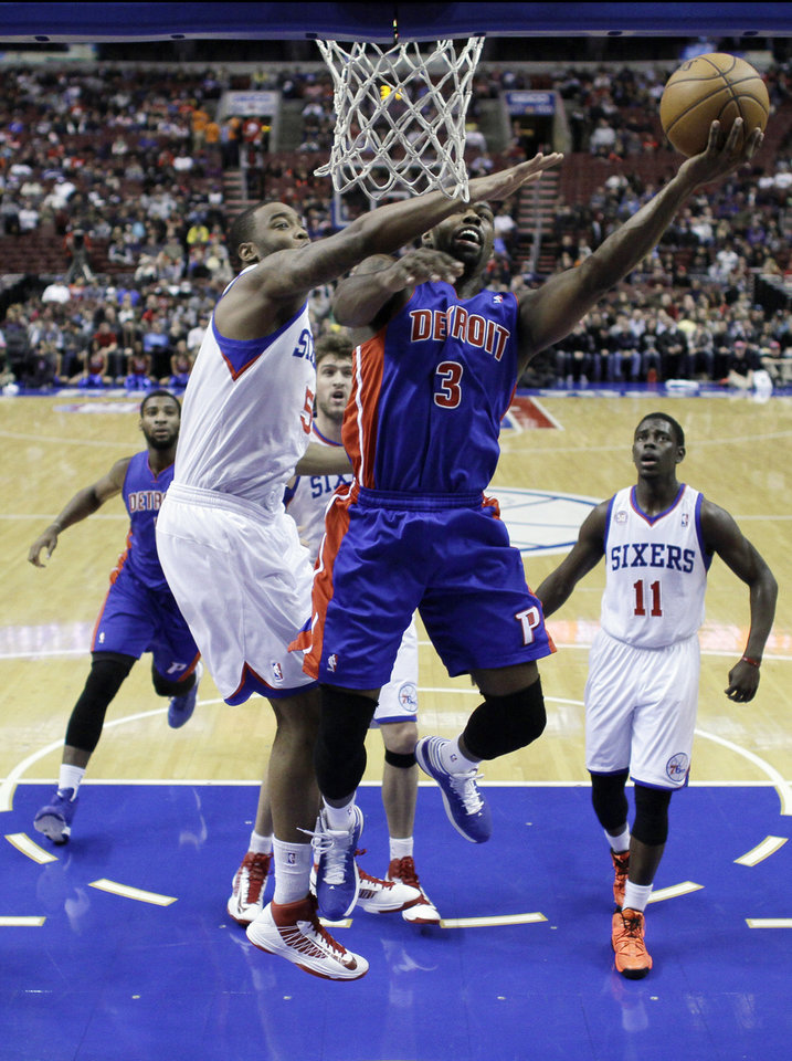 Photo - Detroit Pistons' Rodney Stuckey, right, goes up for a shot past Philadelphia 76ers' Arnett Moultrie in the first half of an NBA basketball game, Monday, Dec. 10, 2012, in Philadelphia. (AP Photo/Matt Slocum)