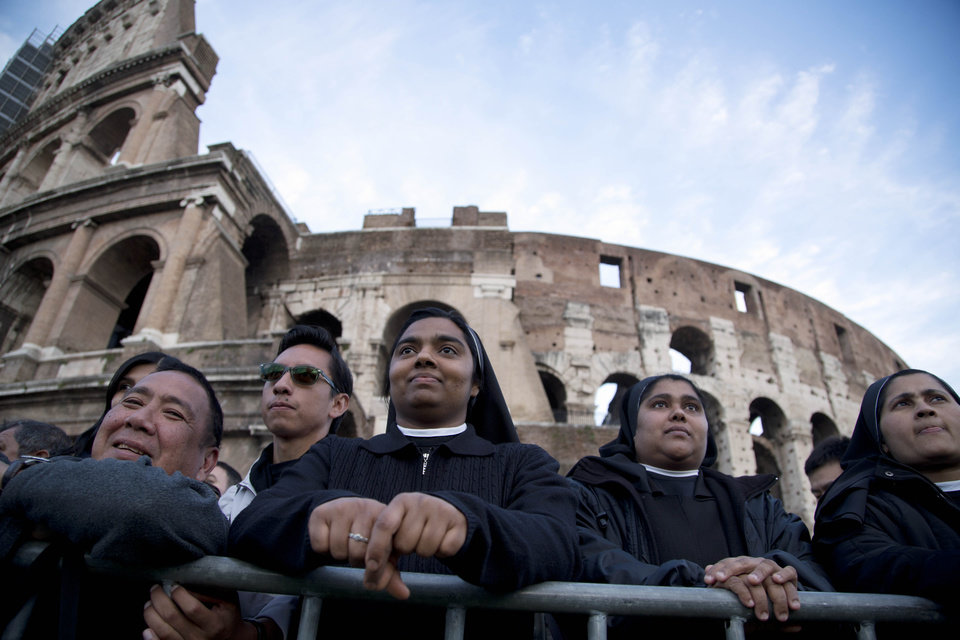 Photo - Nuns and faithful wait for the start of the Via Crucis (Way of the Cross) torchlight procession to be celebrated by Pope Francis in front of the Colosseum on Good Friday in Rome, Friday, April 18, 2014. (AP Photo/Gregorio Borgia)