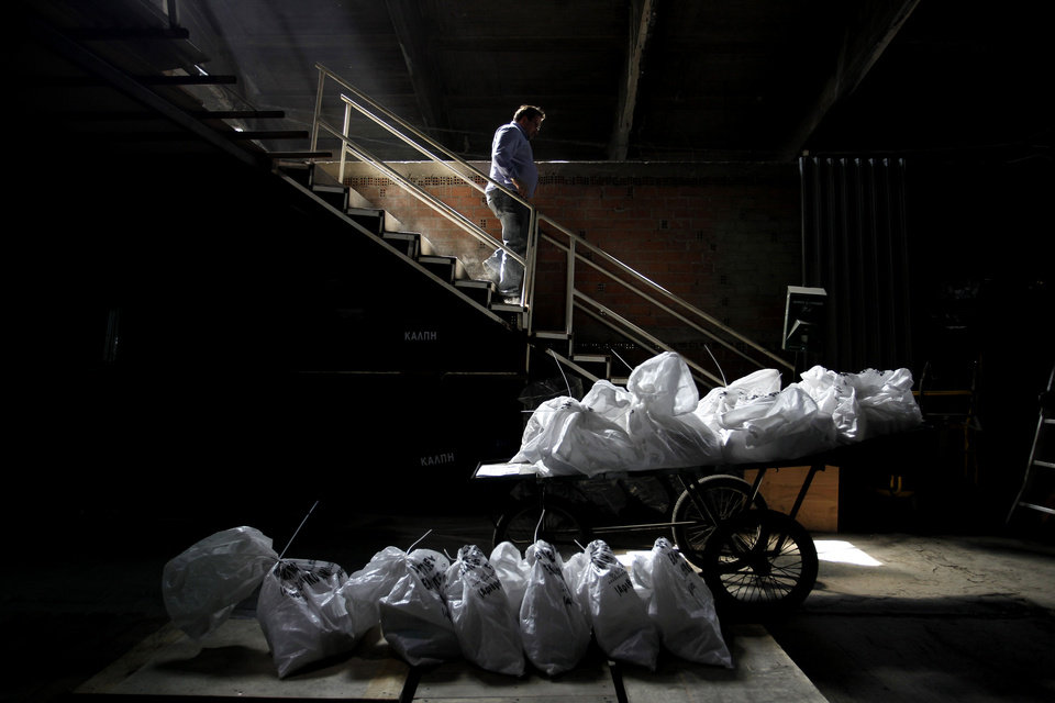Photo -   A worker goes down stairs in front of bags of voting papers in Athens' municipality's warehouse, before delivering them to the polling stations around Athens, on Thursday, May 3, 2012. Greeks head to the polls in early general elections on May 6 .(AP Photo/Petros Giannakouris)