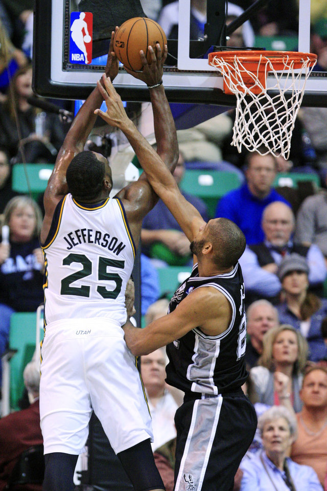 Photo - Utah Jazz center Al Jefferson (25) shoots as San Antonio Spurs forward Tim Duncan, right, defends in the second quarter during an NBA basketball game, Wednesday, Dec. 12, 2012, in Salt Lake City. (AP Photo/Rick Bowmer)