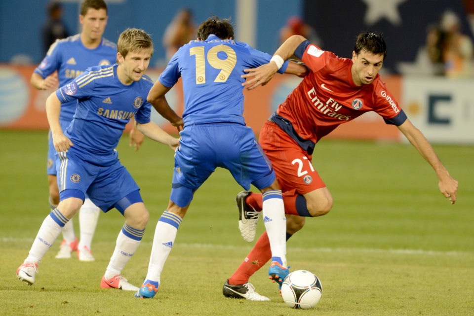 Photo -   Paris Saint-Germain's Javier Pastore, right, gets past Chelsea FC's Paulo Perreira, center, while Chelsea FC's Marko Marin looks on during the second half of their soccer match at Yankee Stadium in New York, Sunday, July 22, 2012. The game ended in a 1-1 draw. (AP Photo/Henny Ray Abrams)