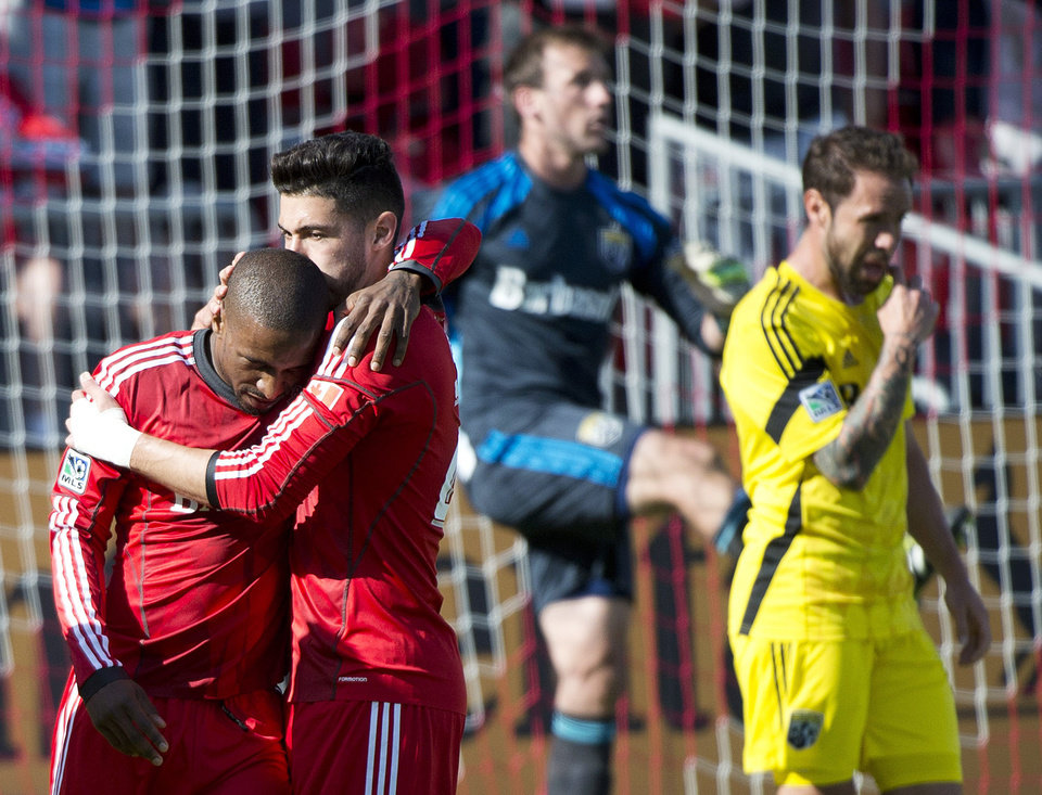 Photo - Toronto FC forward forward Jermain Defoe, left, celebrates his goal with teammate Jonathan Osorio, near Columbus Crew players during the first half of an MLS soccer game in Toronto on Saturday, May 31, 2014. (AP Photo/The Canadian Press, Nathan Denette)