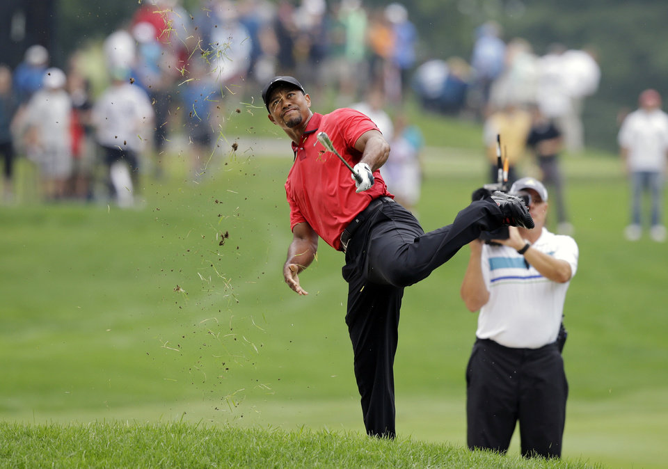 Photo - Tiger Woods makes an awkward follow through after hitting from the lip of a fairway bunker on the second hole during the final round of the Bridgestone Invitational golf tournament Sunday, Aug. 3, 2014, at Firestone Country Club in Akron, Ohio. (AP Photo/Mark Duncan)