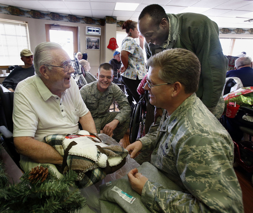 World War II U.S. Navy veteran John Calvin Bailes talks with, from left, National Guardsman Samuel Wilson, Airman Lynne Lee and Col. Jeff Pickard at a holiday party Friday at the Norman Veterans Center given by the 507th Air Refueling Wing at Tinker Air Force Base. PHOTOS BY STEVE SISNEY, THE OKLAHOMAN