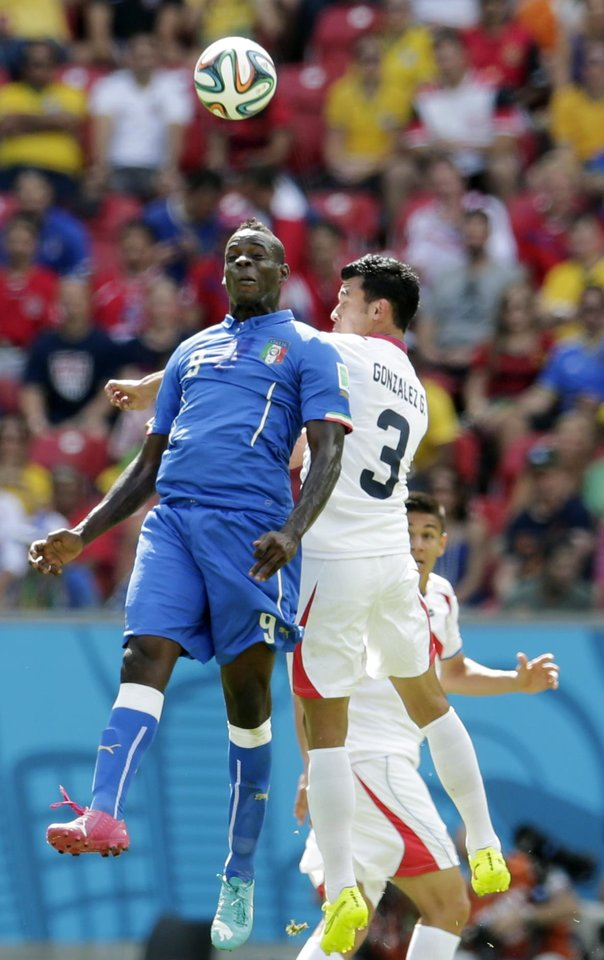 Photo - Italy's Mario Balotelli, left, and Costa Rica's Giancarlo Gonzalez head the ball during the group D World Cup soccer match between Italy and Costa Rica at the Arena Pernambuco in Recife, Brazil, Friday, June 20, 2014.  (AP Photo/Petr David Josek)