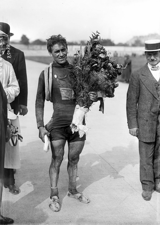 Photo - In this undated photo provided by the WielerMuseum Roeselare, Belgian cyclist and 1914 Tour de France winner Philippe Thys, center, holds a bouquet of flowers. On June 28, 1914, 145 riders lined up to start the 12th running of the Tour de France, including a record seven previous Tour champions. The same day, a continent away, a political assassination took place that would have consequences unimaginable to the riders as they pedaled across Normandy to Le Havre. (AP Photo/Wielermuseum)