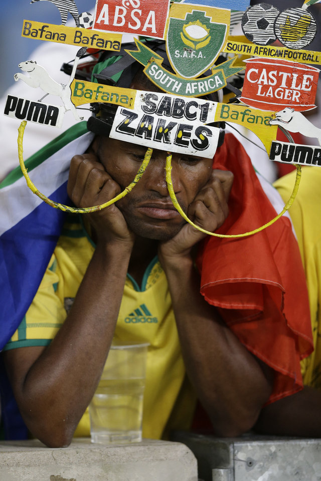 Photo - A South Africa fan reacts as his team is knocked out of the African Cup of Nations after losing to Mali on penalties in their quarterfinal soccer match, at Moses Mabhida Stadium in Durban, South Africa, Saturday, Feb. 2, 2013. (AP Photo/Rebecca Blackwell)