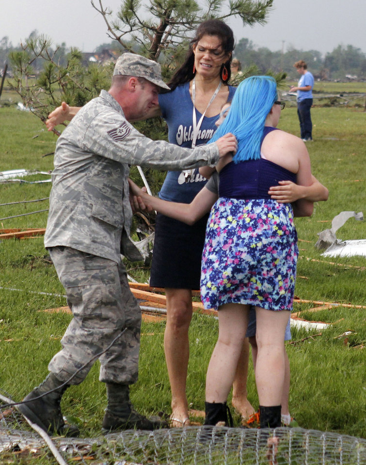 T. Sgt. Robert Raymond, left, runs to embrace his son Ethan, 11, with his daughter Lily, 17, at Briarwood Elementary school after a tornado destroyed the school in south Oklahoma City, Monday, May 20, 2013. Near SW 149th and Hudson. By Paul Hellstern, The Oklahoman