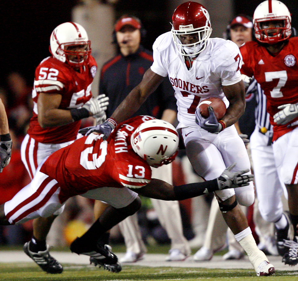 Photo - Oklahoma's DeMarco Murray (7) is forced out of bounds by Nebraska's P.J. Smith (13) during the second half of the college football game between the University of Oklahoma Sooners (OU) and the University of Nebraska Cornhuskers (NU) on Saturday, Nov. 7, 2009, in Lincoln, Neb.