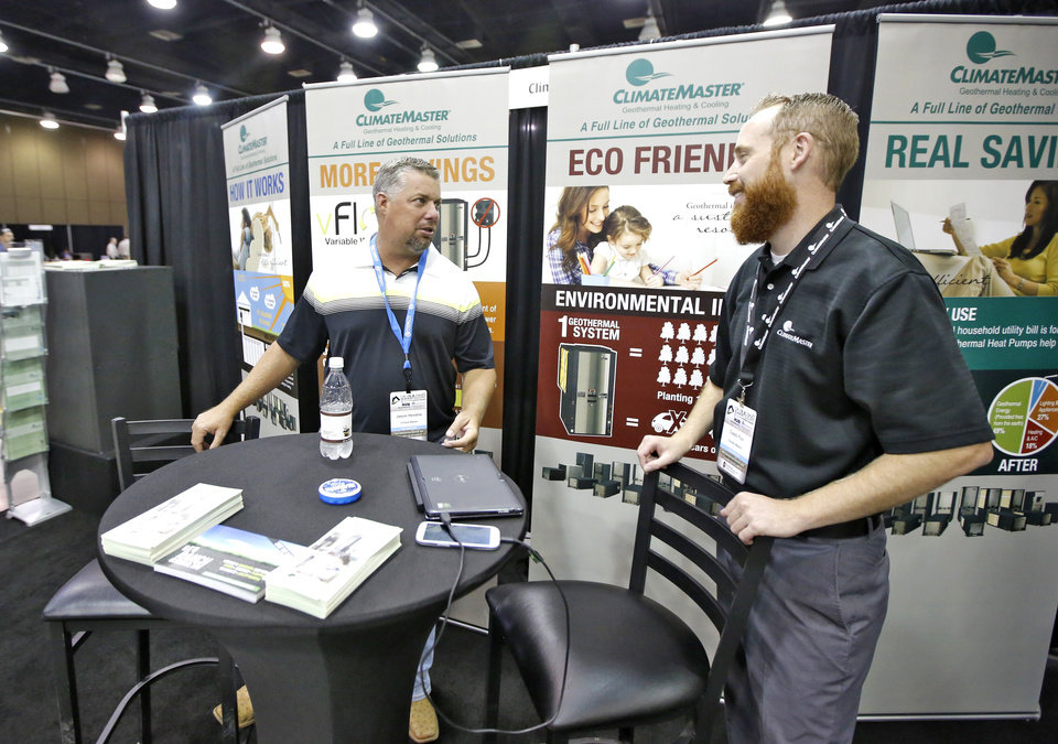 Photo -  Jason Hendrix, ClimateMaster sales team member, and ClimateMaster marketing coordinator Caleb Fox operate a booth at the Oklahoma Building Summit & Expo at Cox Convention Center. [PHOTO BY STEVE GOOCH, THE OKLAHOMAN]