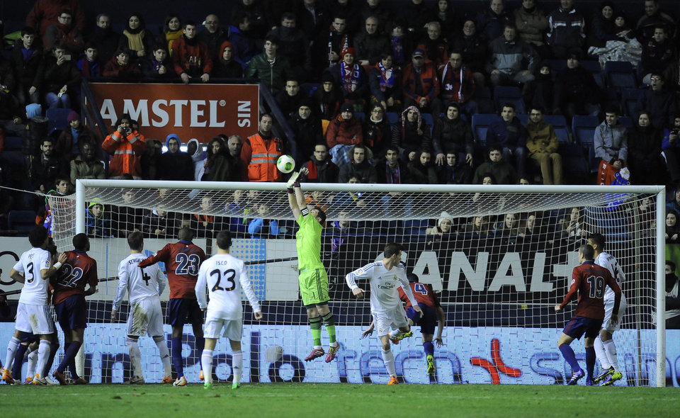 Photo - Real Madrid's goalkeeper Iker Casillas, center, treaches for the ball during their Spanish Copa del Rey round-16 second leg soccer match between Osasuna and Real Madrid , at El Sadar stadium, in Pamplona northern Spain on Wednesday, Jan. 15, 2014. (AP Photo/Alvaro Barrientos)