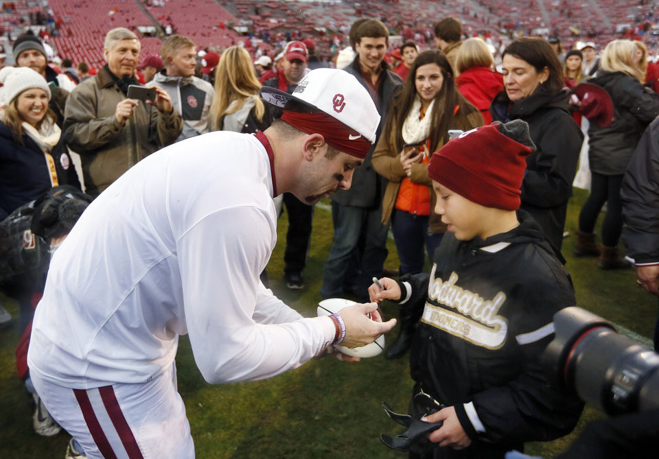 Photo - Oklahoma's Baker Mayfield (6) signs an autograph for a fan after the Bedlam college football game between the Oklahoma Sooners (OU) and the Oklahoma State Cowboys (OSU) at Gaylord Family - Oklahoma Memorial Stadium in Norman, Okla., Saturday, Dec. 3, 2016. OU won 38-20. Photo by Nate Billings, The Oklahoman