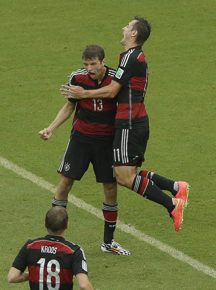 Photo - Germany's Thomas Mueller (13) is congratulated by teammates avert he scored during the group G World Cup soccer match between the USA and Germany at the Arena Pernambuco in Recife, Brazil, Thursday, June 26, 2014. (AP Photo/Hassan Ammar)