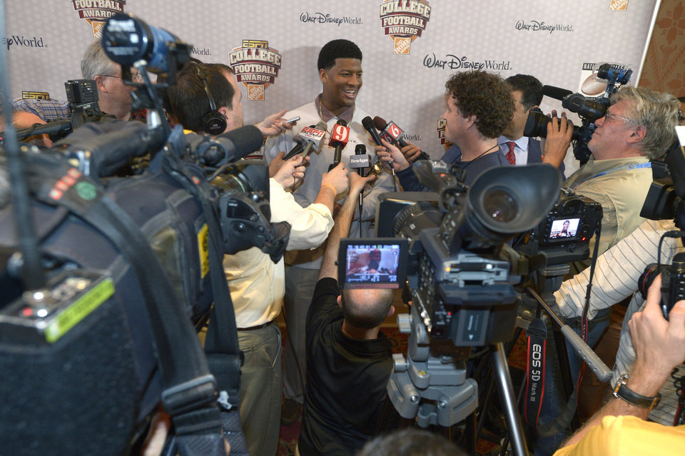 Photo - FILE - In this Dec. 11, 2013, file photo, Florida State quarterback Jameis Winston, center, answers questions during a media availability prior to the College Football Awards show in Lake Buena Vista, Fla. Winston has the opportunity to accomplish what only one other player has achieved _ win consecutive Heisman trophies. He enters the season as the leading candidate with defending national champion Florida State likely starting the year ranked No. 1. (AP Photo/Phelan M. Ebenhack, File)