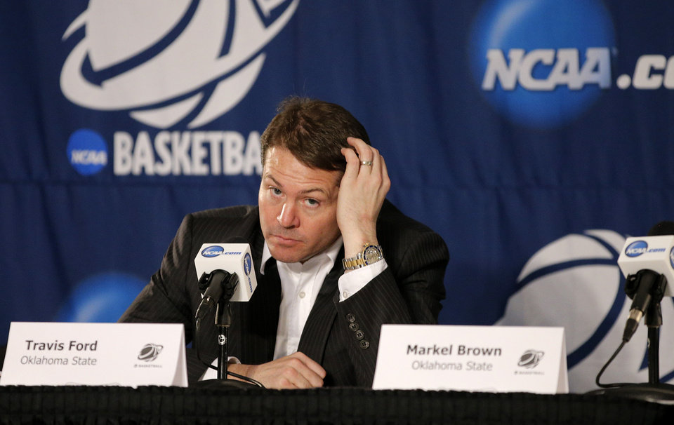 Photo - OSU coach Travis Ford listens to a question in a press conference after a second round game of the NCAA men's college basketball tournament at Viejas Arena in San Diego, between Oklahoma State and Gonzaga Friday, March 21, 2014. Gonzaga won 85-77. Photo by Bryan Terry, The Oklahoman