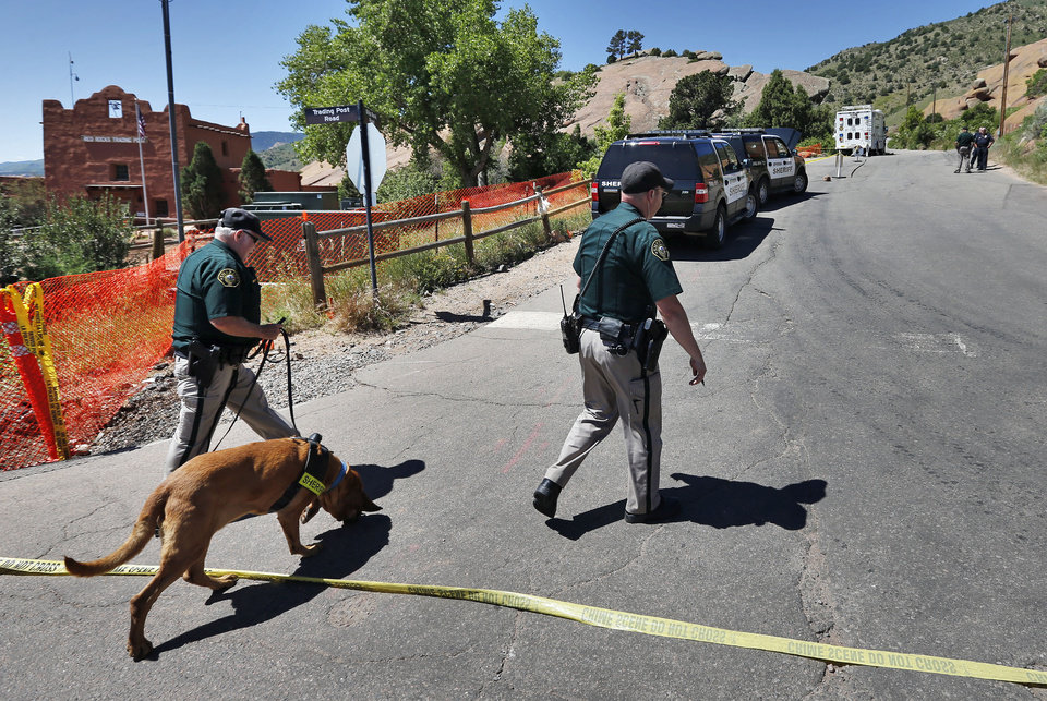Photo - A police K-9 team walks into the closed off south entrance to Red Rocks Amphitheater, in Morrison, Colo., Friday June 20, 2014. Authorities were searching Friday for a gunman who shot and wounded three people at the end of a benefit concert at the popular outdoor amphitheater near Denver on June 19. (AP Photo/Brennan Linsley)