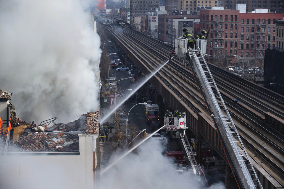 Photo - Firefighters respond to a fire on 116th Street in Harlem after a building exploded in huge flamesleading to the collapse of at least one building and several injuries, Wednesday, March 12, 2014, in New York. (AP Photo/John Minchillo)