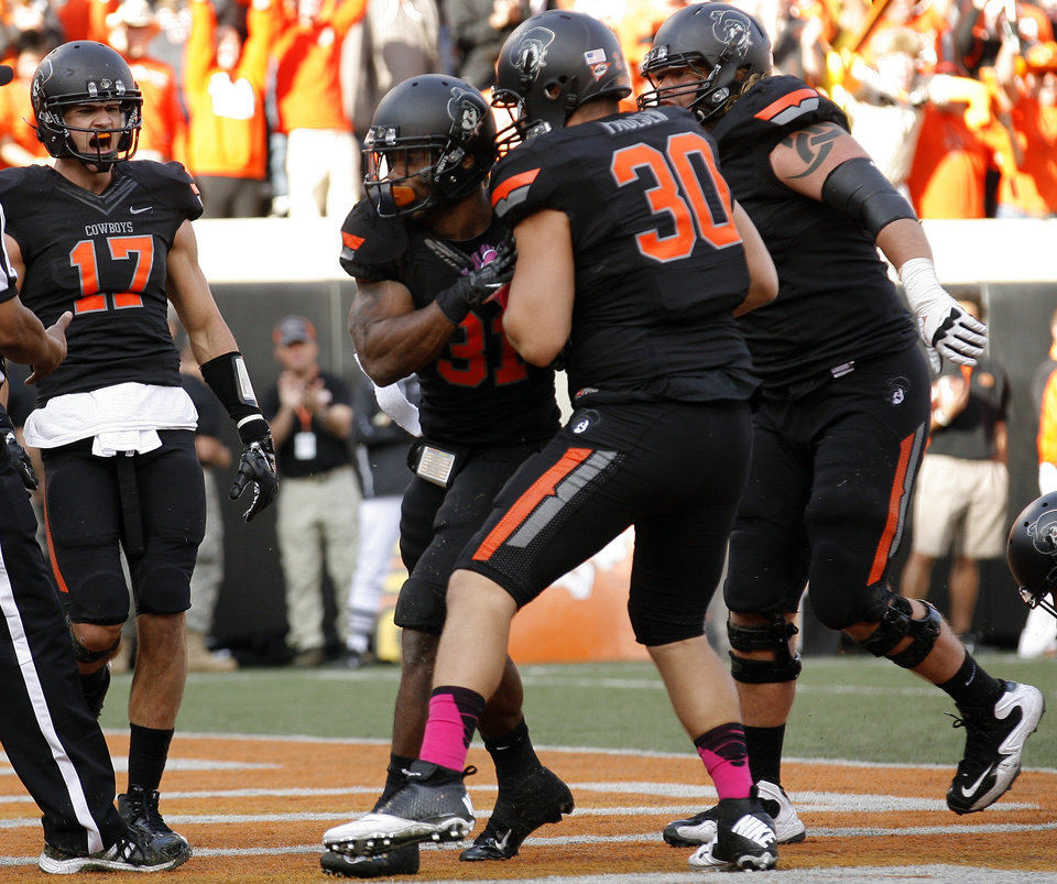 Photo - Oklahoma State celebrates a Jeremy Smith (31) touchdown during a college football game between Oklahoma State University (OSU) and Texas Christian University (TCU) at Boone Pickens Stadium in Stillwater, Okla., Saturday, Oct. 27, 2012. Photo by Sarah Phipps, The Oklahoman