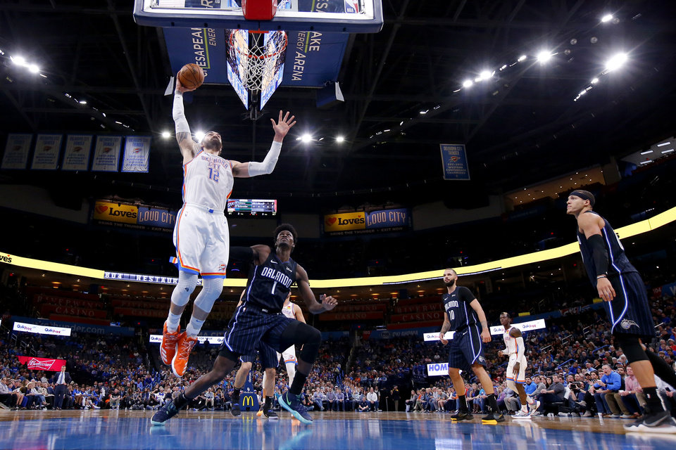 Photo - Oklahoma City's Steven Adams (12) dunks the ball beside Orlando's Jonathan Isaac (1) during an NBA basketball game between the Oklahoma City Thunder and the Orlando Magic at Chesapeake Energy Arena in Oklahoma City, Tuesday, Nov. 5, 2019. Oklahoma City won 102-94. [Bryan Terry/The Oklahoman]