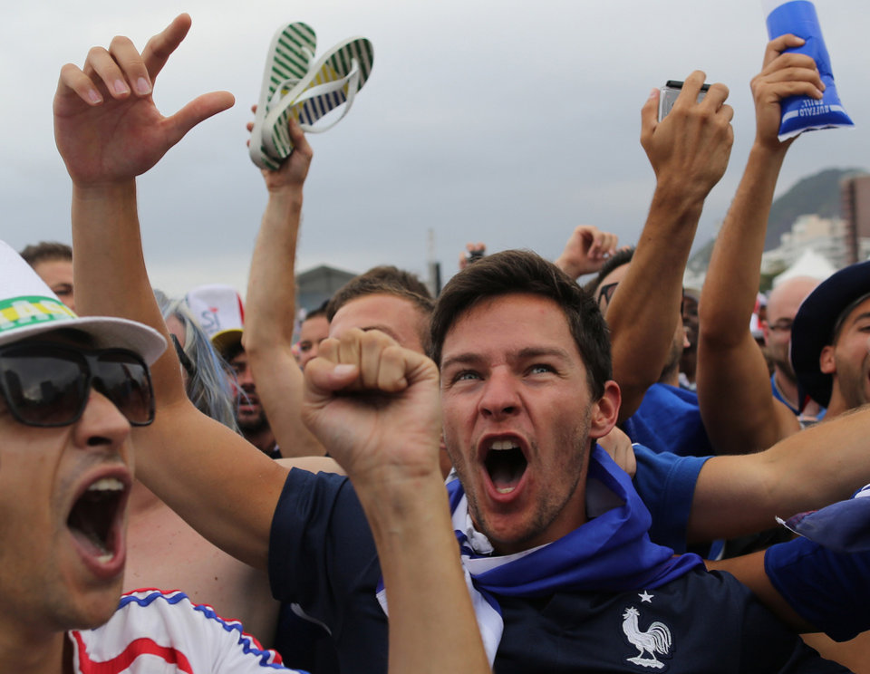 Photo - France soccer fans celebrate the second goal scored by their team as they watch the World Cup round of 16 match of France against Nigeria on a live telecast inside the FIFA Fan Fest area on Copacabana beach in Rio de Janeiro, Brazil, Monday, June 30, 2014. France's Paul Pogba scored with a late header to finally break Nigeria's stubborn resistance and Joseph Yobo scored an own-goal as France won 2-0 to reach the World Cup quarterfinals on Monday. (AP Photo/Leo Correa)